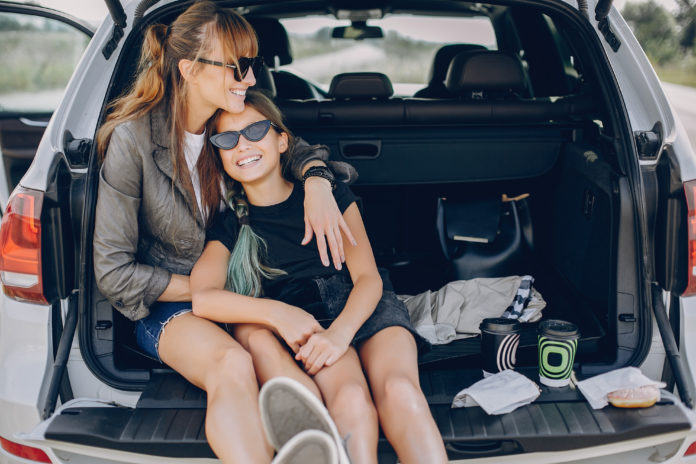 Mom and daughter sitting on tailgate, mothers day gift guide